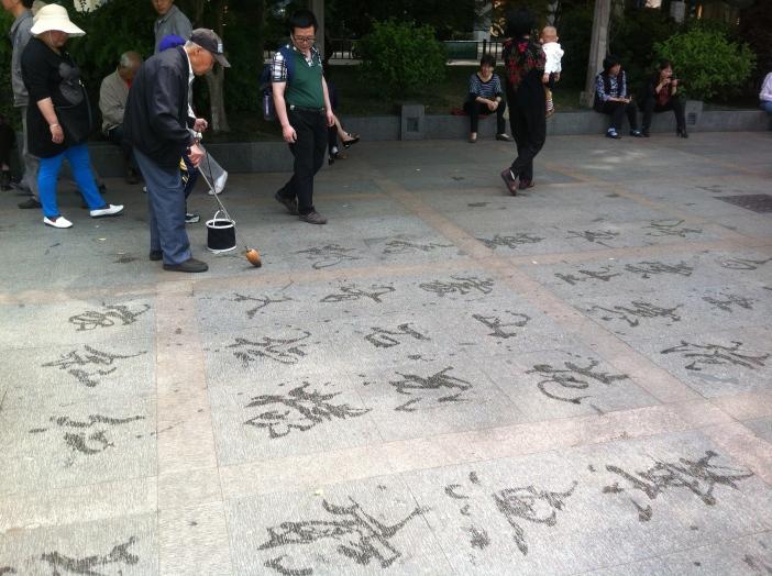 Un hombre escribe carácteres en el suelo con agua. Hangzhou (China).